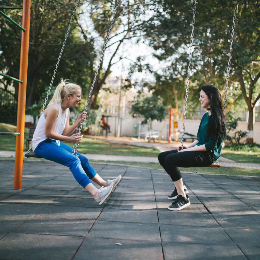 two friends talking and sitting on swings